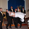 Groomsmen attepting to save the bride and carry her away!