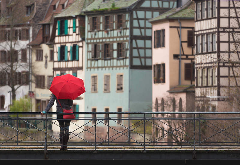 Smiling young woman with umbrella on bridge in Strasbourge
