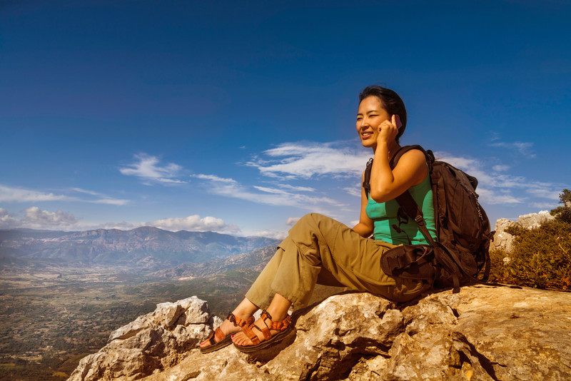 female hiker talking on cell phone
