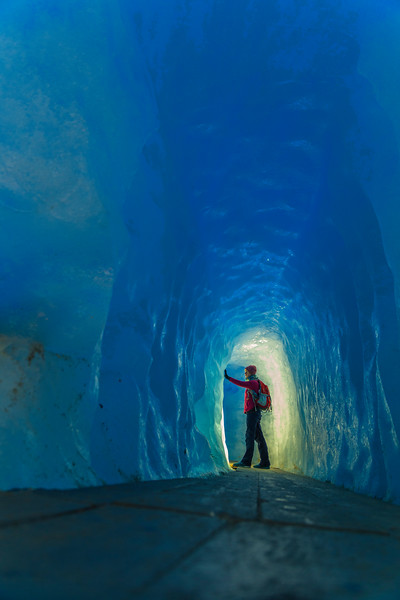 A tourist in the Ice Cave of the Rhône Glacier, Switzerland.