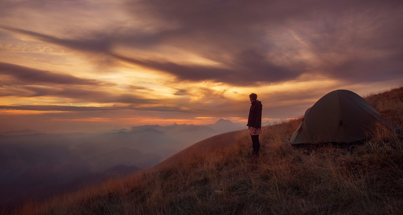 woman with tent at sunset