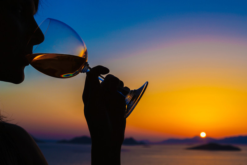 Woman drinking wine at sunset