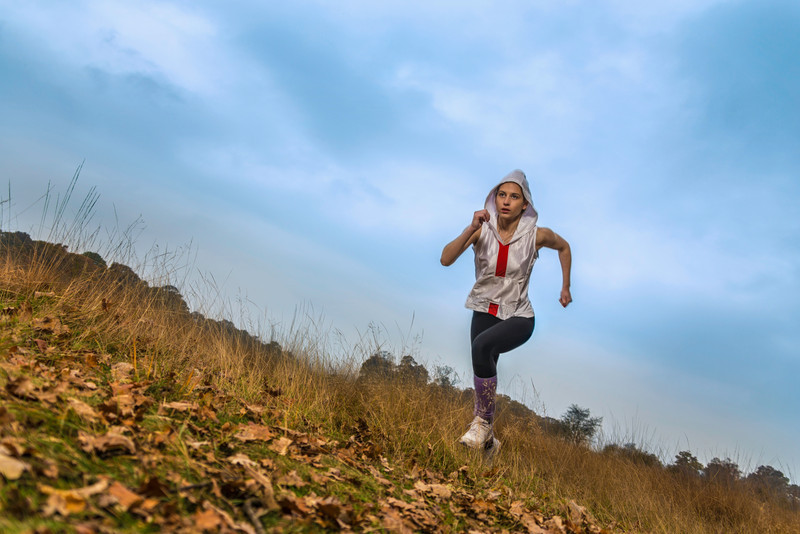 A young female athlete running in a park