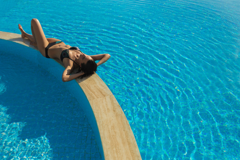 Young woman sunbathing by pool