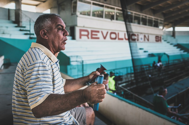A man supports his local junior high baseball team with his self-built bicycle-pump-air-horn. The huge baseball stadium built by the Soviets is mostly empty.