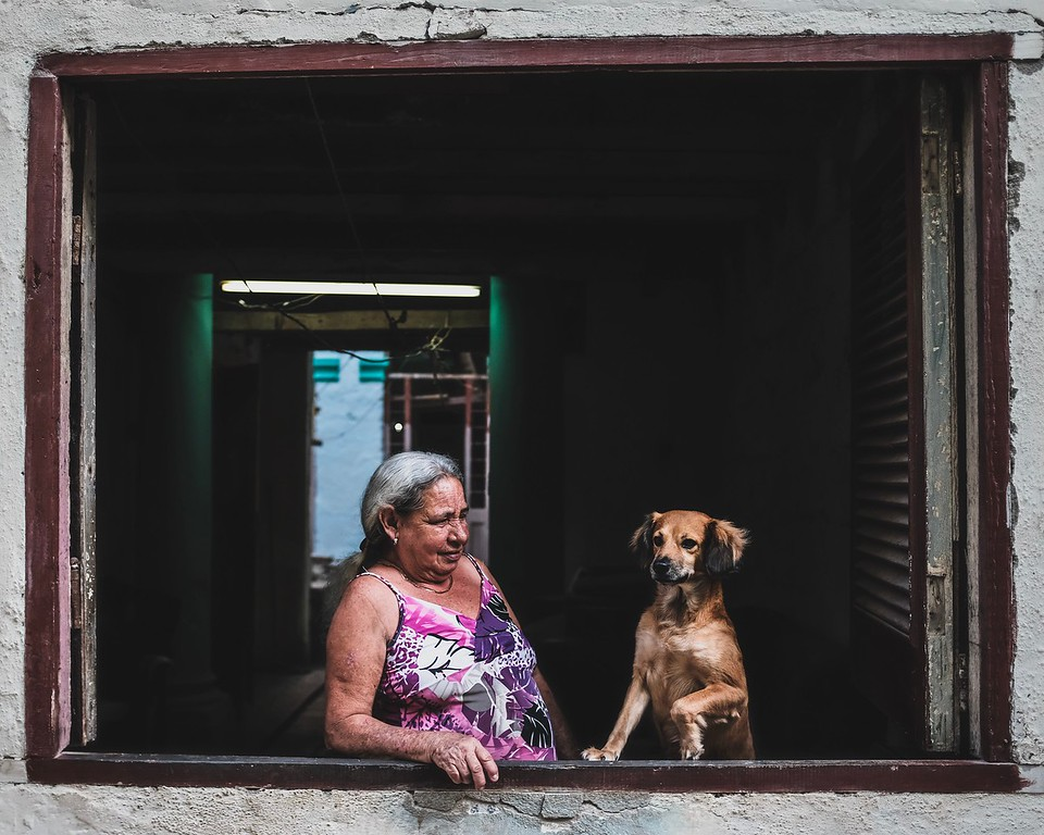A Cuban woman makes sure her dog performs properly for passersby.