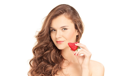 Pretty brunette woman holding a strawberry