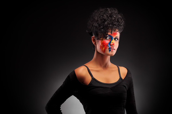 Portrait of a beautiful Indian with her face covered in paint against dark background