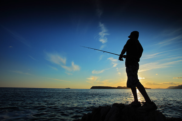 Fisherman catching fish at sunset in Croatia