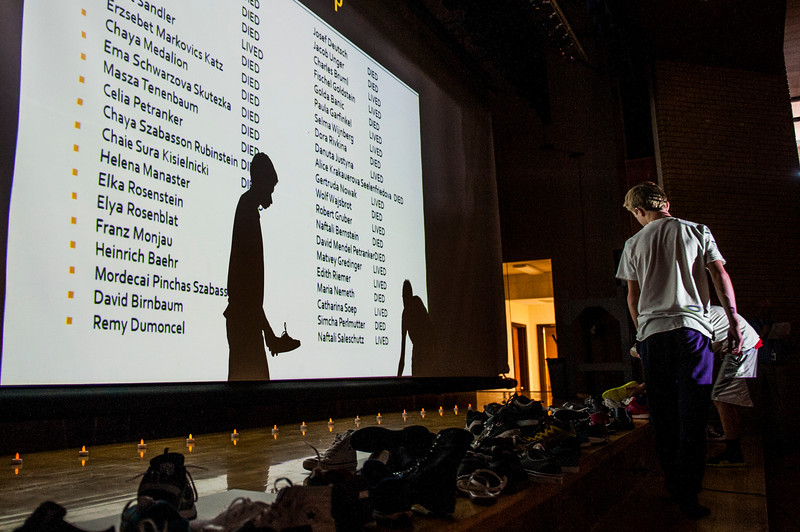 Brigg Malan, an 8th grader at Sunset Junior High, places his shoe at the front of the gym stage to symbolize the death of a Holocaust victim during a Holocaust Memorial Ceremony in Sunset on June 1, 2015.