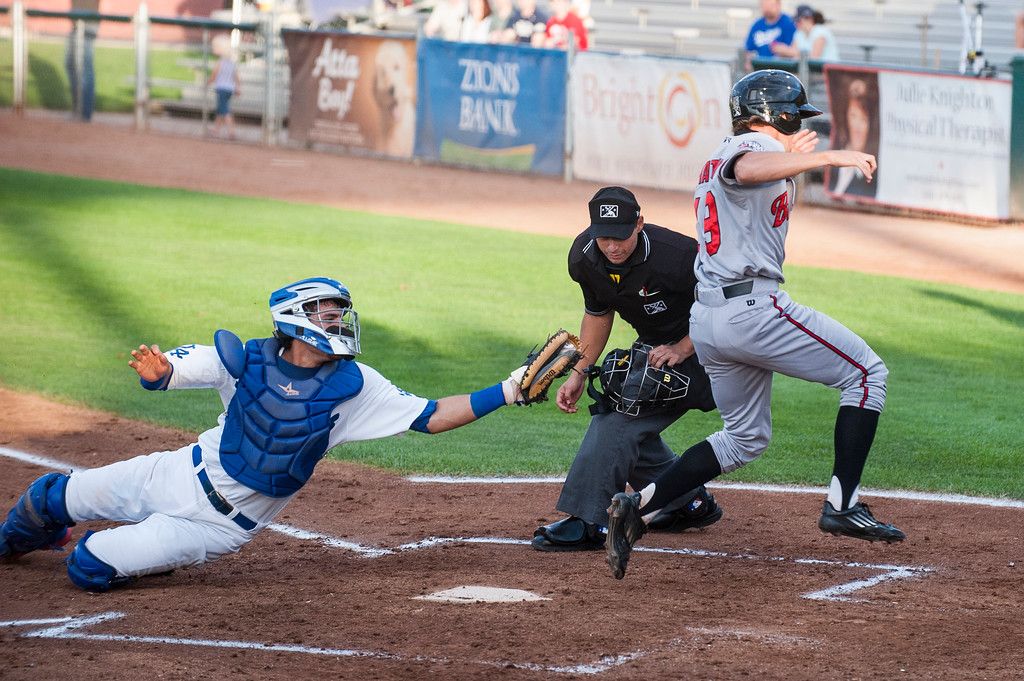 Ogden catcher, Gersel Pitre (13), misses tagging out Billings player, Mitch Piatnik (19), <br /> after he stole home plate for the first run of the game at Lindquist Field in Ogden on August 15, 2015. Piatnik's teammate, Blake Trahan, was caught in a pickle between first and second base, allowing Piatnik extra time to score the run.