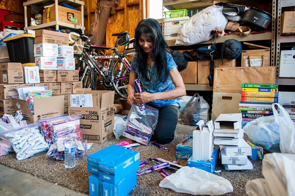 Teresita Bunn unpacks toothbrushes from boxes and repacks them into plastic bags to save on space in Washington Terrace on April 28, 2015. A group of 20 people are going to Ghana to perform service and deliver supplies and everything must fit in large suitcases.