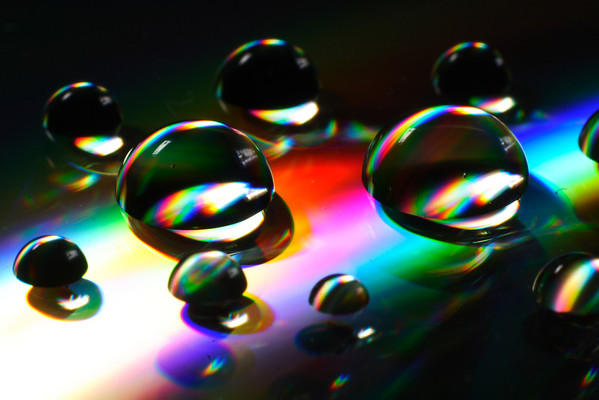 Droplets on a CD.  The reflective surface, combined with refraction from the plastic and the drops, leads to a lot of colour