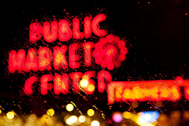 The landmark Public Market neon sign and clock at the Pike Place Market in Seattle. As seen through raindrops on a car windshield at night, it can be seen as a archetype image for Seattle.