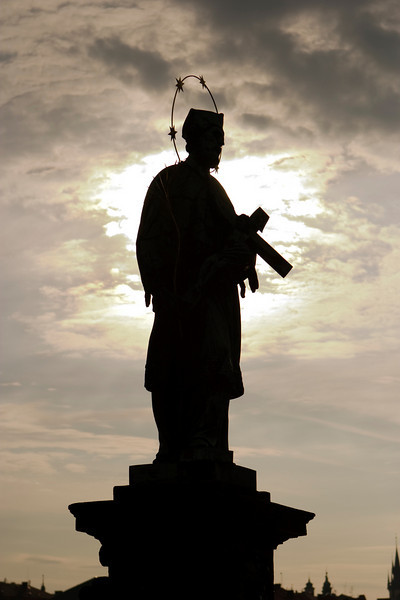 A statue of a saint with a copper halo on the Charles Bridge in Prague is silhouetted against a cloudy sky.