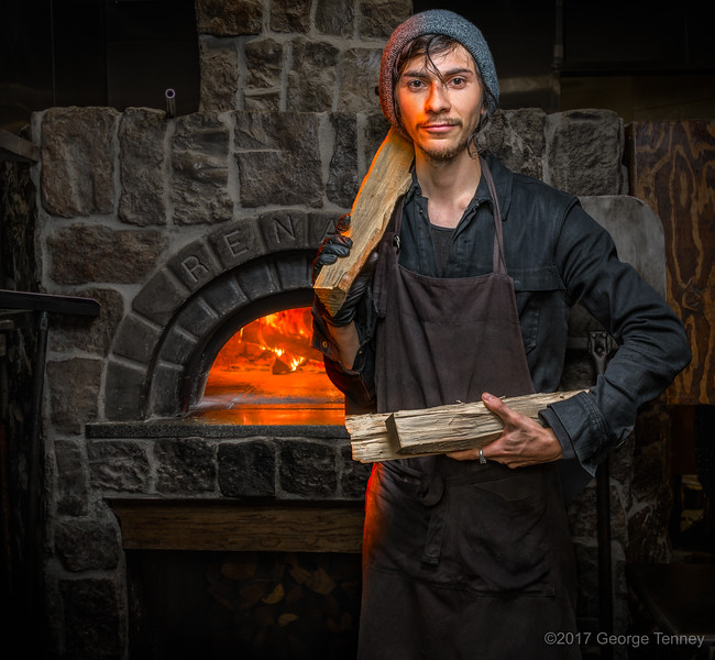 Portrait-of-chef-holding-firewood-by-brick-oven-flames