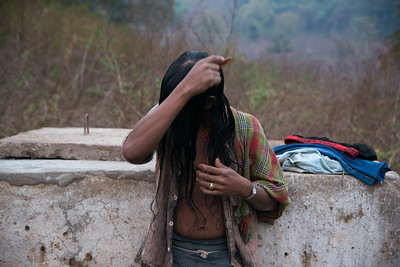 A man combs his hair after a bath. The Dongria Kondh are particular about hair and traditional attire. Males decorate their hair, ears, and nose with ornaments.