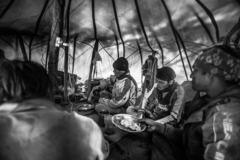 Migrant workers having lunch inside a tent at Chushul village, about an hour's drive from Leh. Lunch break lasts for an hour. The food is basic, barely adequate for the harsh climate – rice, dal and some vegetables cooked on a stove in their tents.