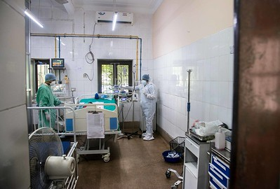 Inside an isolation room, staff in PPE kits attend to a Covid-positive child who is 35 days old.