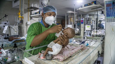 A nurse in the Neonatal Intensive Care Unit (NICU) is giving medicine to a neonate. Despite seeing staff on duty falling to 40 per cent of normal, the hospital soldiers on in providing services for children-left.