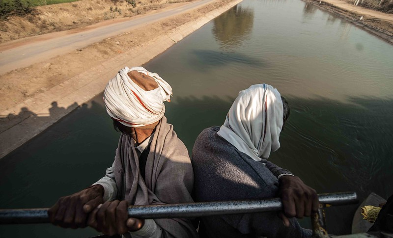 Two passengers riding on the side of the train look on as they crosses an irrigation canal.