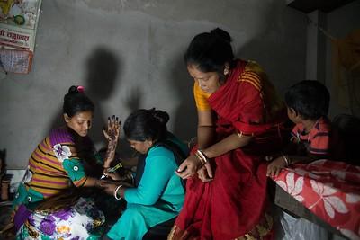 A relative is designing Mehendi on Priyanka's hand.