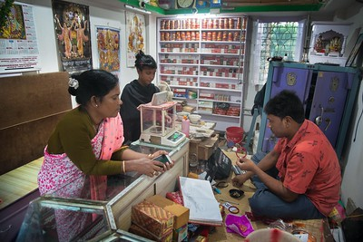 """Pushpa Mondol is buying """"Pola"""" from a local Jewellery shop. Shakha & Pola are a symbol of a married woman in Bengali culture. This custom is the most popular and accepted in rural areas mostly. She said """"I never imagined, I had to do this by myself. Very unfortunate for me."""""""
