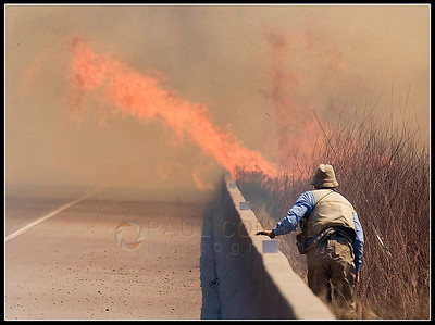© Paul Conrad/Pablo Conrad Photography  Fly fisherman Tom Greenup of Wisc., watches flames encroach upon Highway 82 as he and two others barely escape the flames near Carbondale, Colo. His friend Larry Garfinkle of Thousand Oaks, Calif., was severely burned while escaping.