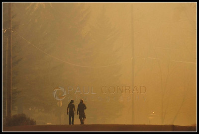 © Paul Conrad/Pablo Conrad Photography  Two pedestrians walk down County Road 100 near Equestrian Way during the 100 Road brush fire east of Carbondale, Colo.