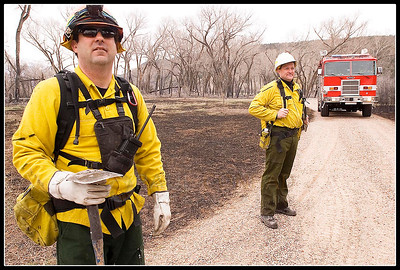 © Paul Conrad/Pablo Conrad Photography  Aspen volunteer firefighters Chris Olsen, left, and Mike Lyons check for hot spots in the Roaring Fork Preserve off County Road 100 near Carbondale. With the 100 Road fire nearly contained, fire fighters worked to extiquish hot spots and fall burned trees.