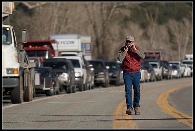 © Paul Conrad/Pablo Conrad Photography  With the afternoon traffic backing up behind him, Monroe Summers of Basalt Colo., walks towards the El Jebel light after parking his truck and cattle trailer a quarter mile back on Highway 82. Summers said he was concerned about his cattle that were in a lot where the wildland fire was burning.