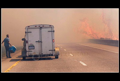 © Paul Conrad/Pablo Conrad Photography  A man watches the encroaching flames after stopping on Highway 82 one mile east of Ranch at Roaring Fork.