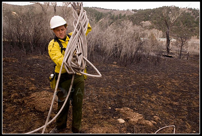 © Paul Conrad/Pablo Conrad Photography  Aspen volunteer fire fighter Mike Lyons winds up a hose after dousing a hot spot in the Roaring Fork Preserve subdivision.