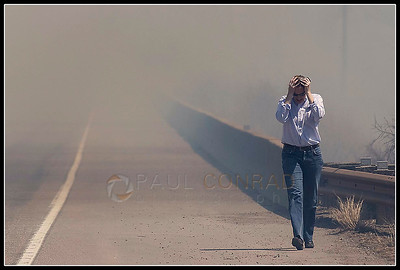© Paul Conrad/Pablo Conrad Photography  Adrian Rowberry of Carbondale, Colo., walks in dismay after watching an encroaching wildland fire threaten her neighborhood along Highway 82.