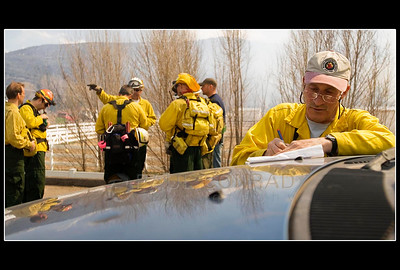© Paul Conrad/Pablo Conrad Photography  Aspen volunteer fire fighter Ron Baar, left, takes notes as other Aspen fire fighters prepare to help battle the fire.