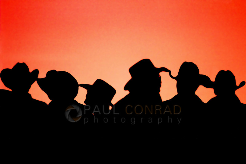 Bullnanza in Hooper, Utah - Cowboys wait at the chutes during sunset for the bull riding competition to begin during Bullnanza held at the Hooper Arena in Hooper, Utah. (© Paul Conrad/Paul Conrad Photography)