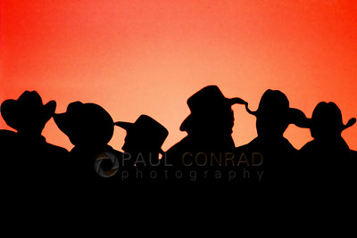 © Paul Conrad/Pablo Conrad Photography - Cowboys wait at the chutes during sunset for the bull riding competition to begin during Bullnanza held at the Hooper Arena in Hooper, Utah.