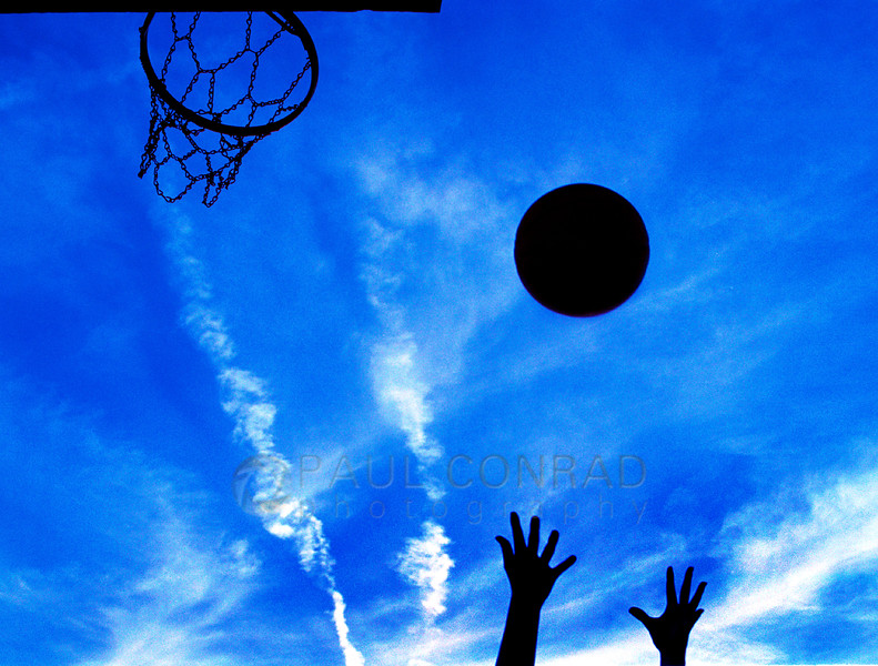Reaching for the Rebound - A girl reaches for a rebound while playing a pick-up game of basketball at a Bowling Green, Ky., park. (© Paul Conrad/Paul Conrad Photography)