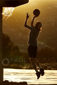 © Paul Conrad/Pablo Conrad Photography - A Colorado Mountain College student plays some basket ball on the courts of the Spring Valley campus outside Glenwood Springs during a brilliant sunset.