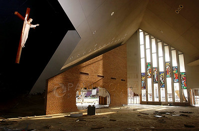 © Paul Conrad/Pablo Conrad Photography - A crucifix watches over the remains of St. Paul's Catholic Church in Pass Christian, Miss., on month after Hurricane Katrina roared through the region. The stained glass windows of the Apostles remained intact while the others shattered from the wind. The pews and marble alter were never found.