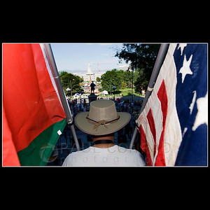 """© 2008 Paul Conrad/Pablo Conrad Photography  Gary Anderson of Lakewood, Colo., stands on the steps of the Colorado State Capitol in Denver, Colo., while holding Palestinian flag, left, and 48 star U.S. flag as hundreds gather for a protest rally and march during the Democratic National Convention on Sunday morning Aug. 24, 2008.   Anderson says he is opposed to the Iraqi war and that """"nations can have a moral integrity, but empires cannot."""""""