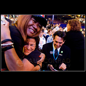 © 2008 Paul Conrad/Pablo Conrad Photography  Colorado delegates Blanca O'Leary of Aspen, bottom, and Julia Hicks of Westminster hug while Brian Gonzales of Basalt sends text messages after the Colorado delegation declared their votes for Barack Obama towards the presidential nomination Wednesday afternoon Aug. 27, 2008, during the Democratic National Convention at the Pepsi Center in Denver. Colorado delegates voted 55-17 for Obama.