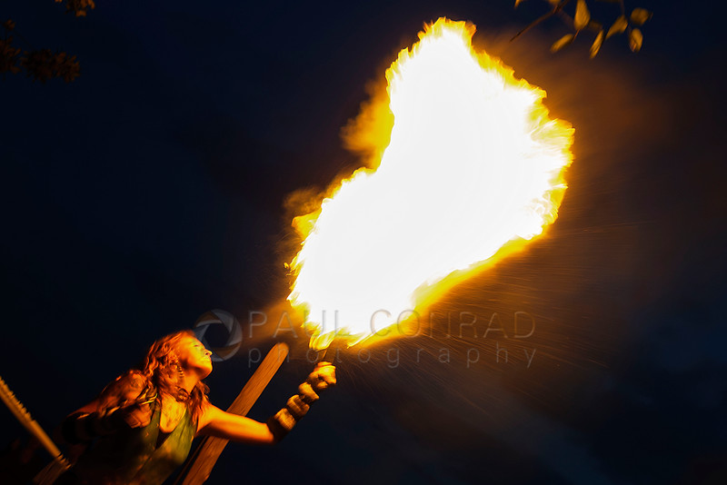 Lindsay McFinland of Bellingham spits a fireball into the sky while performing during sunset at Locust Beach on Sunday evening July 17, 2016, in Bellingham, Wash. A group of artists are attempting to make the third Sunday of each month a meeting time to perform at Locust Beach. (© Paul Conrad/Paul Conrad Photography)
