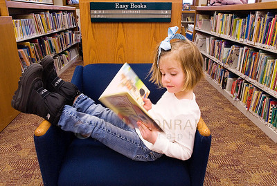 © Paul Conrad/Pablo Conrad Photography - Kicking back for a good read, Lillian Cassidy, 5, of New York City browses through the children's selections at the Evelyn Flug Children's Library at the Pitkin County Library in Aspen, Colo.