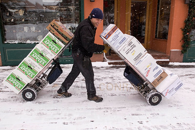 "© Paul Conrad/Pablo Conrad Photography - Laughing as he negotiates snowy streets, Sysco Foods delivery driver Glenn Venegas (cq) of Denver double trucks an order to the Red Onion on the Cooper Avenue Mall in Aspen. ""(Using two hand trucks) saves me time and a trip"" Venegas says, ""so I don't have to spend so much time in this nasty weather."""