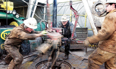 """© Paul Conrad/Pablo Conrad Photography - (l to r) Roughneckers Derek Thompson, Ben Garner, and Chris Thompson use """"tongs"""" to tighten a new length of pipe onto the drill while working the derrick Caza 11 in Mamm Creek area near Rifle, Colo."""