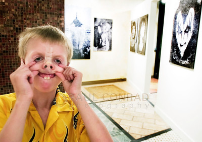 "© Paul Conrad/Pablo Conrad Photography - ""It's only for fun,"" says Jake Floria, 9, of Aspen Colo., while he makes faces in the mirror after taping his nose and ears at the Lynn Goldsmith Gallery in Basalt."