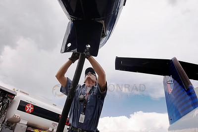 © Paul Conrad/Pablo Conrad Photography - Brian DeWeese of Snowmass Village, Colo., begins filling a United Airlines Dash 8 with aviation fuel before its flight out of the Aspen Pitkin County Airport in Aspen, Colo.