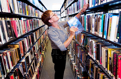 © Paul Conrad/Pablo Conrad Photography - A 15 year veteran of the Basalt, Colo., library, Barb Milnor shelves returned books before opening for business.
