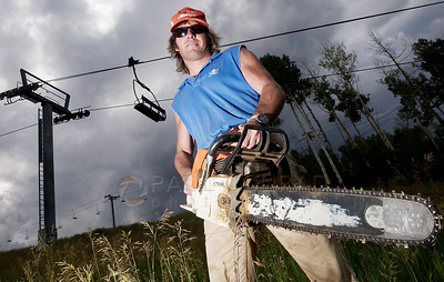 """© Paul Conrad/Pablo Conrad Photography - A ski patroler during the winter and lumberjack by summer, John Brennan of Aspen, Colo., works under the Coney Glade lift on Snowmass Mountain.. Brennan main job is to ensure the slopes are safe by keeping them clear of debris.  He says he likes his job due to the variety. """"It's a good job,"""" says Brennan, """"it changes and I like that."""""""